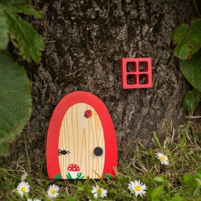 Cherry Tree Garden & Home Fairydoorz  A ruby red wooden fairy door designed by fairydoorz in a set with a matching wooden window.  All weather proofed for outside use.  Perfect for against decking steps, a fence, wall or tree!  These doors can be used as indoor fairydoorz too!  The design is a wood effect grain with ladybird & toadstool.  Ready to welcome in any fairies & bright enough to stand out in any garden!  High quality magical decorations to brighten up your day!