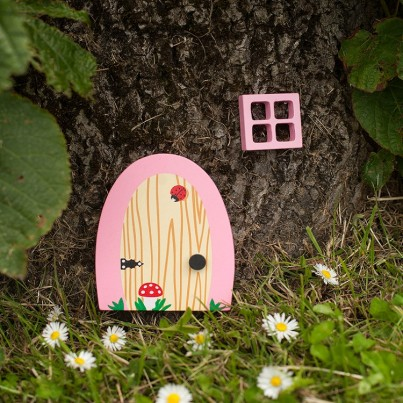 Pink Blossom Garden & Home Fairydoorz  A bubble gum pink wooden fairy door designed by fairydoorz in a set with a matching wooden window.  All weather proofed for outside use.  Perfect for against decking steps, a fence, wall or tree!  These doors can be used as indoor fairydoorz too!  The design is a wood effect grain with ladybird & toadstool.  Ready to welcome in any fairies & bright enough to stand out in any garden!  High quality magical decorations to brighten up your day!