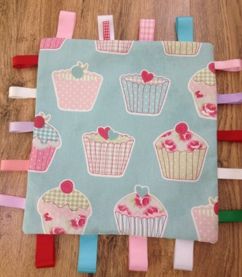 Cup cake comfort taggie blanket 12 ins x 12 ins with various ribbons. The fabric is 100% cotton and a quality soft white fleece backing. Ideal for teething and inquisitive babies.